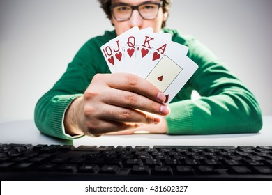 Handsome young man in green pullover sitting at desk with computer keyboard and showing playing card fan