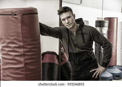 Handsome young man in gym next to punching bag, wearing training suit