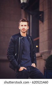 Handsome young man with hairstyle in black fashionable clothes posing in city