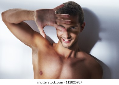 Handsome young man with hand in front of the face. Portrait with nice effect of light. Studio shoot over white background