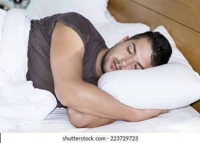 Handsome young man happily sleeping in white bed