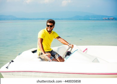Handsome young man happy tanned, brunette driving a speedboat on the beach, wearing a yellow polo shirt, shorts, sunglasses, casual wear stylish lifestyle, beautiful smile, sunny day, tropical island
