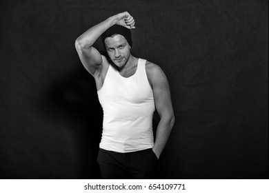 handsome young man in hat, sexy muscular guy portrait on dark background with raised hand, black and white