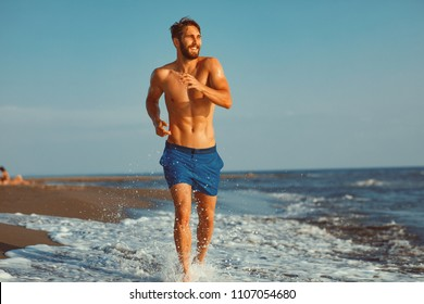 Handsome young man having fun on the beach by the sea