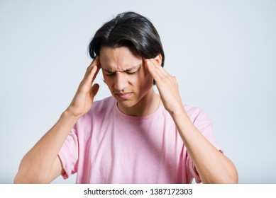 handsome young man with headache, hipster, studio photo on gray background