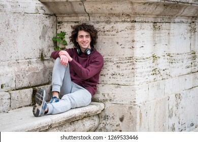 Handsome young man with headphones around his neck relaxing in front of stone wall