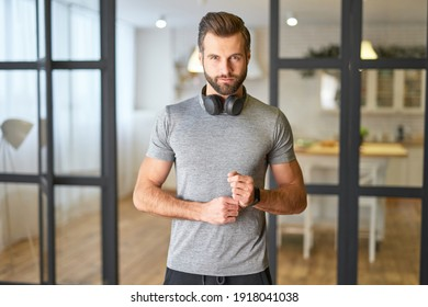 Handsome young man with headphones standing in living room