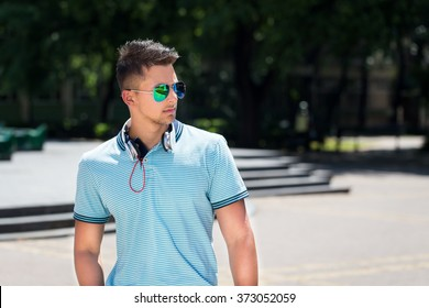 handsome young man with headphones standing on the street in summer