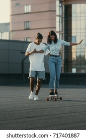 handsome young man helping his girlfriend to ride skateboard