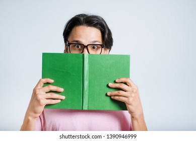 handsome young man hiding behind books on his head, hipster, studio photo on gray background