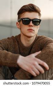 Handsome young man hipster with sunglasses with hairdo in pullover on the street