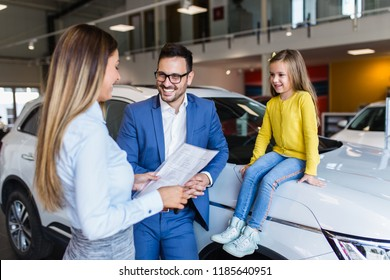 Handsome young man with his cute little daughter choosing a new car at car showroom.