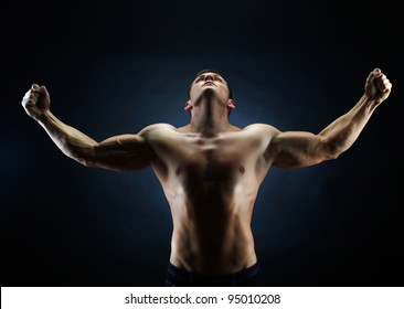 Handsome young man with his hands raised up victoriously against black background