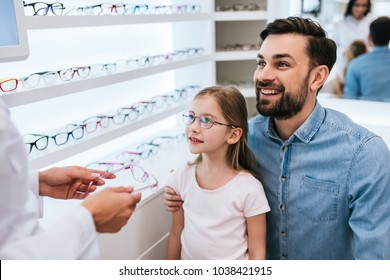 Handsome young man and his little cute daughter are choosing the best apropriate eyeglasses in modern ophthalmology clinic. Dad and daughter with doctor ophthalmologist.