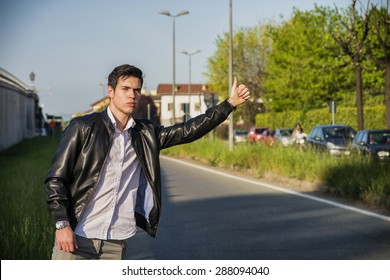 Handsome young man, a hitchhiker waiting for car on roadside in city, wearing black leather jacket