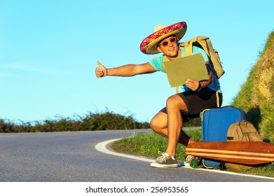 Handsome young man hitch-hiking along a rural mountain road. Hiker guy with luggage and longboard try to stop a car holding paper with copy space.