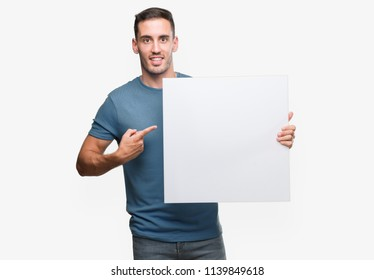 Handsome young man holding advertising banner very happy pointing with hand and finger
