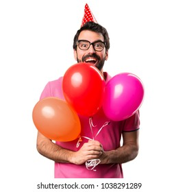 Handsome young man holding balloons over isolated white background