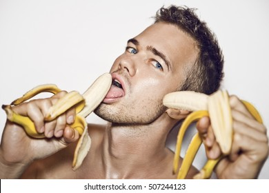 handsome young man holding a banana in both hands with his mouth open