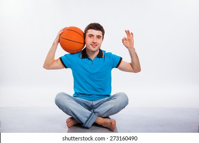 Handsome young man holding a basketball against a white background