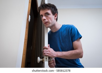 Handsome young man holding door open and listening or eavesdropping to whatever is happening in the next room. Wears blue t-shirt against white background.