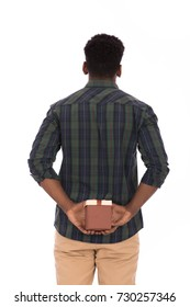 Handsome young man holding a gift box behind his back and looking to white background, guy wearing caro shirt and beige pants