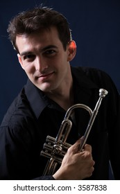 Handsome young man holding his trumpet wearing black on black background