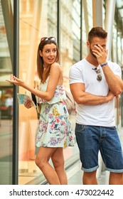 A handsome young man is holding his head because his beautiful girlfriend want to shopping in Budapest, Hungary.