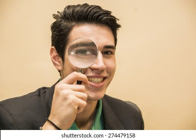 Handsome young man holding a magnifying glass to his eye with a happy friendly smile conceptual of a detective searching for clue