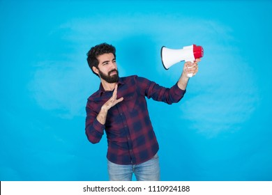 Handsome young man holding a megaphone, looking very upset because the sound is very loud, standing on a blue background.