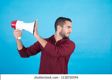 Handsome young man holding a megaphone, and covering it by his hand trying to shut it down, standing on a blue background.