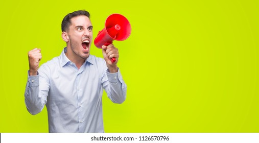 Handsome young man holding microphone annoyed and frustrated shouting with anger, crazy and yelling with raised hand, anger concept