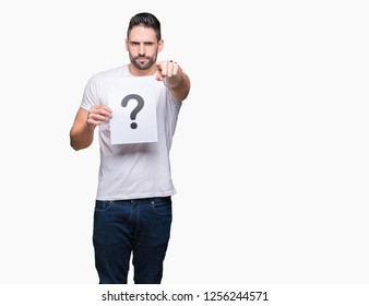 Handsome young man holding paper with question mark over isolated background pointing with finger to the camera and to you, hand sign, positive and confident gesture from the front