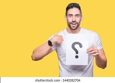 Handsome young man holding paper with question mark over isolated background with surprise face pointing finger to himself