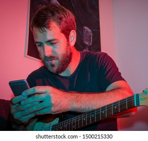 Handsome Young Man Holding Phone and Playing Guitar