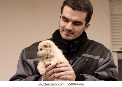Handsome young man holding a puppy