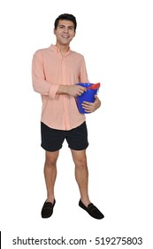 Handsome young man holding a sand pail and a toy shovel