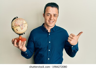 Handsome young man holding small world ball pointing thumb up to the side smiling happy with open mouth