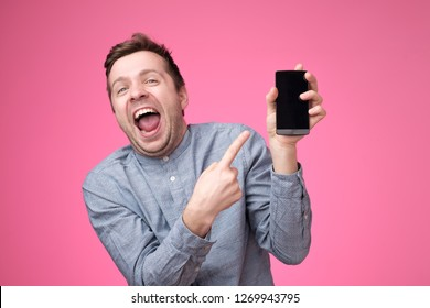 Handsome young man holding smartphone, showing gadget to camera, isolated over pink background. He is laughing on joke in internet.