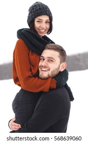 Handsome young man holding a young woman in his arms. Winter