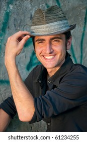 handsome young man holds his hat, smiling