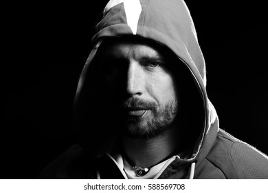 Handsome young man with hoodie and toothpick in shadow