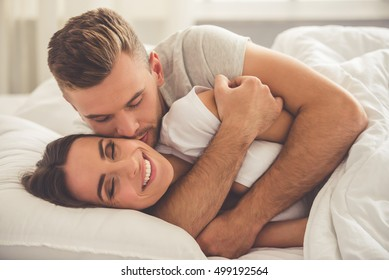 Handsome young man is hugging and kissing his beautiful smiling wife in cheek while they both are lying in bed in the morning