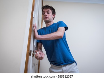 Handsome young man hurriedly shutting door. Perhaps someone coming from next room. Wears blue t-shirt against white background.