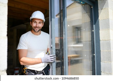 handsome young man installing bay window in new house construction site