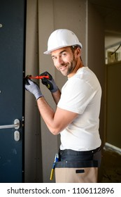 handsome young man installing a door in a new house construction site