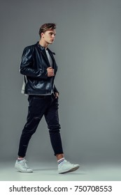 Handsome young man isolated. Fashionable  man in leather jacket is walking on grey background.