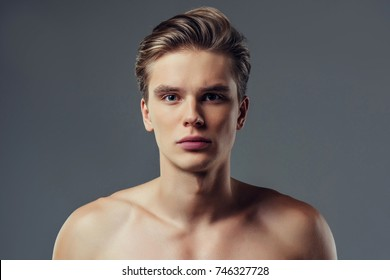 Handsome young man isolated. Portrait of shirtless muscular man is standing on grey background and looking at camera.