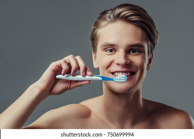 Handsome young man isolated. Portrait of shirtless muscular man is standing on grey background with toothbrush and toothpaste in hand and smiling. Men care concept.