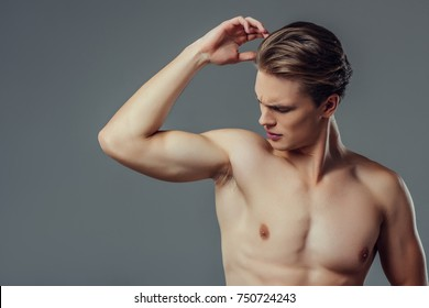 Handsome young man isolated. Portrait of shirtless muscular man is standing on grey background. Feel the smell of sweat. Men care concept.